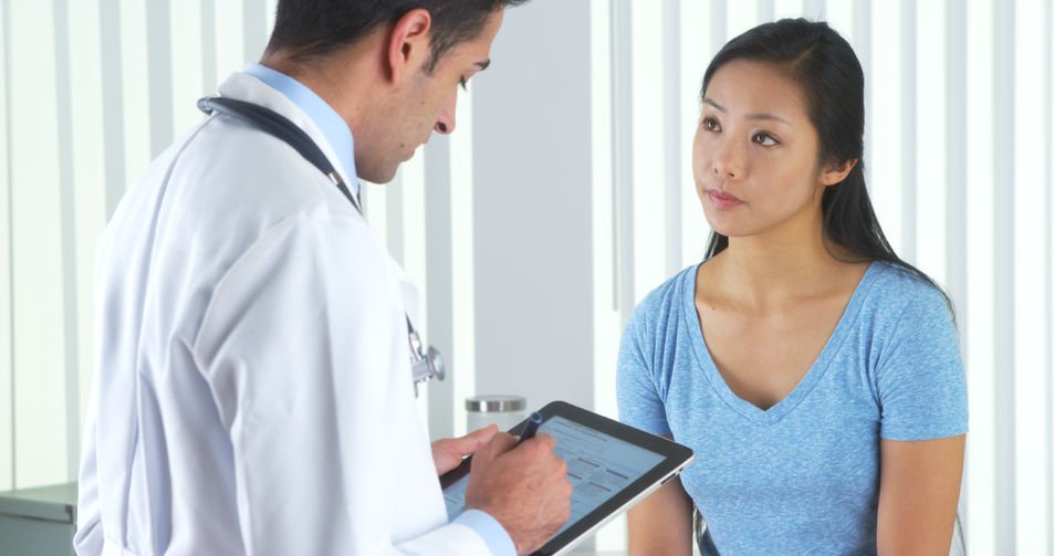 33806165 - hispanic doctor asking asian patient questions