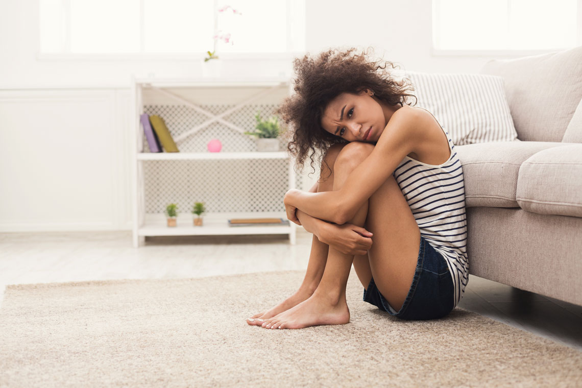 sad-african-american-woman-on-floor-at-home