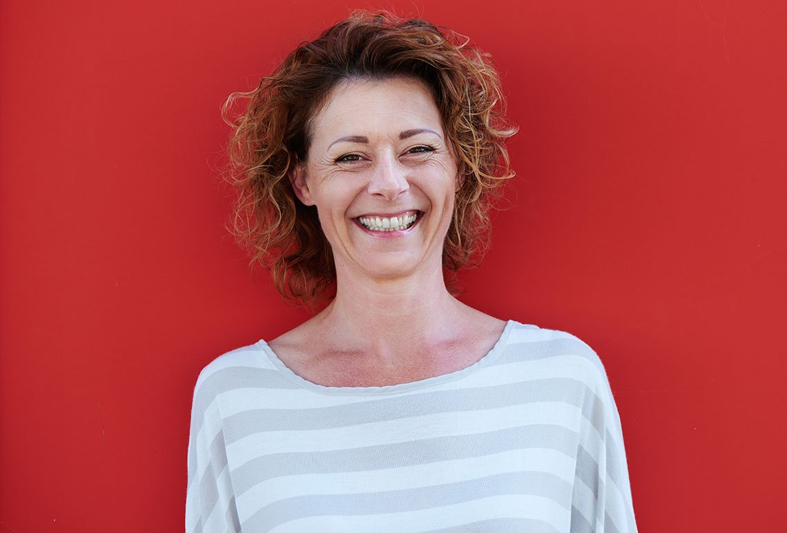 smiling-older-woman-with-curly-hair-against-red-PC4V9W8